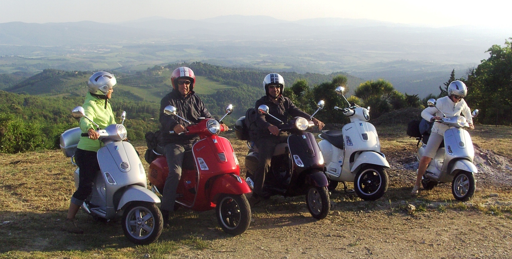 a group of friends happy at the end of their journey by Vespa